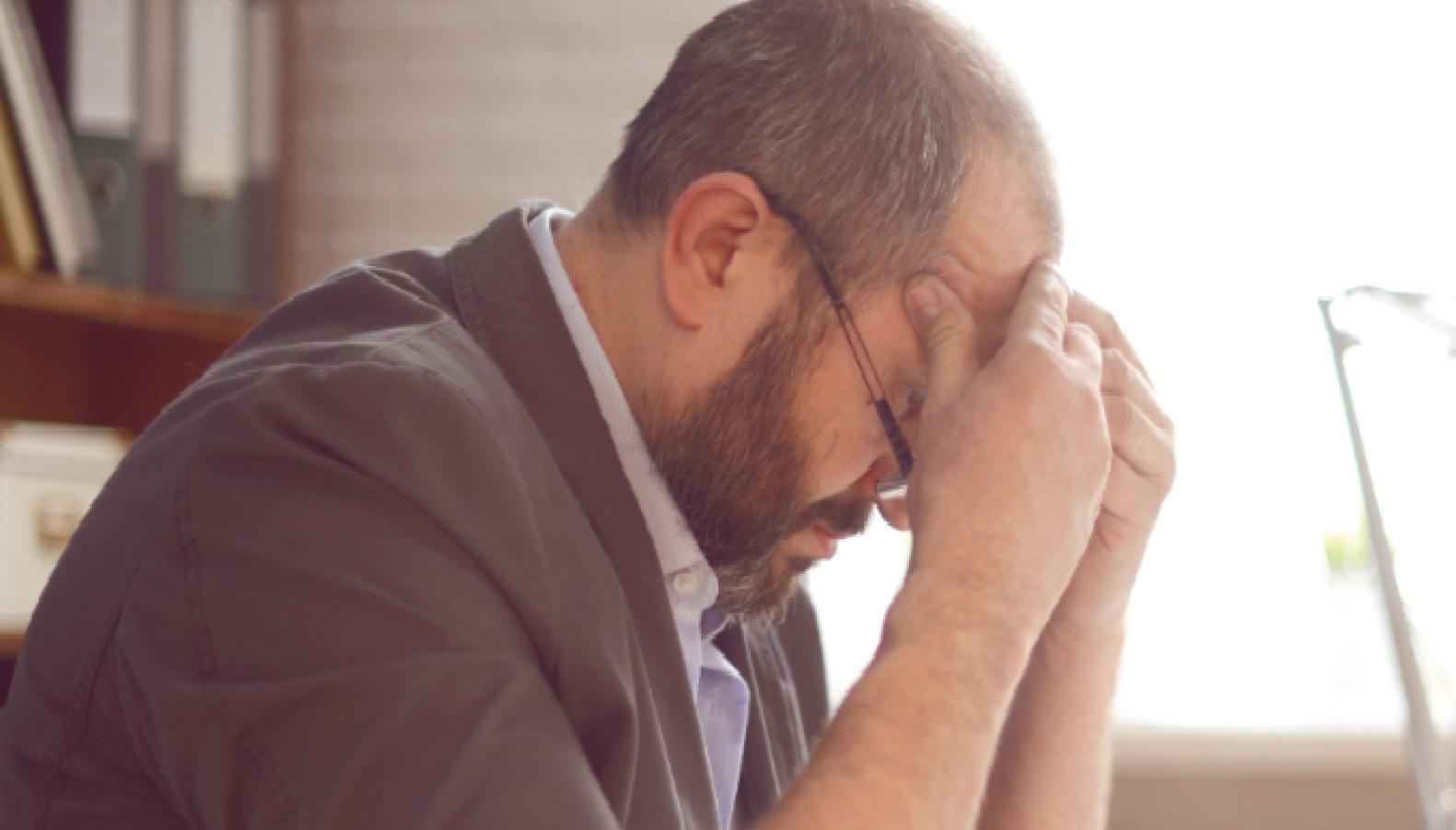 Mand med gråt hår og briller tager sig stresset på panden