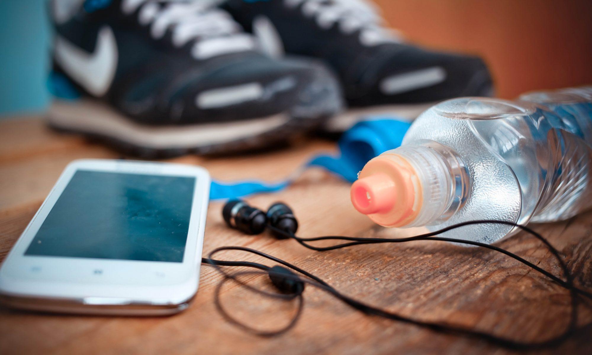 Sorte sportssko, vandflaske og en mobil ligger på en træbænk