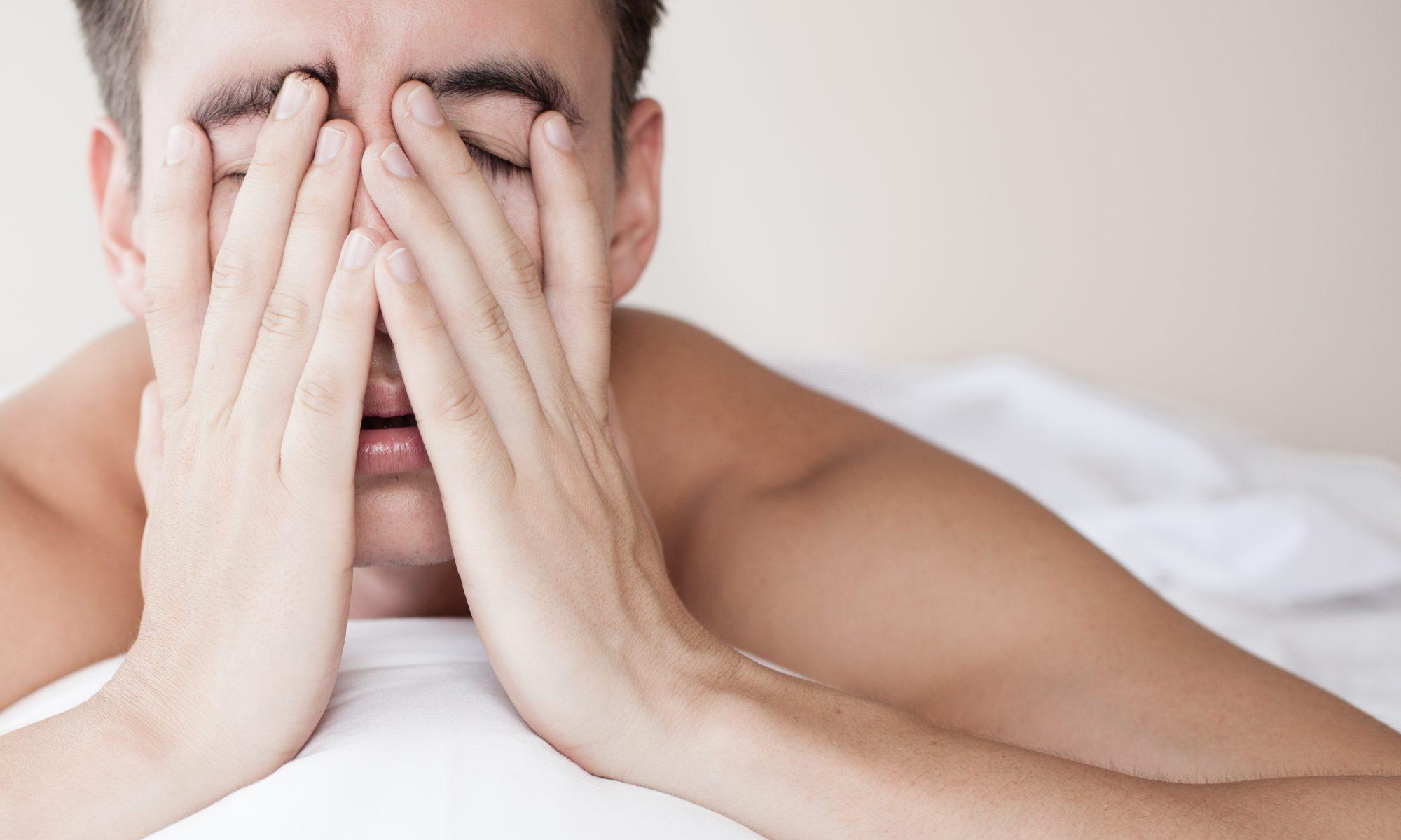 Ung mand vågner op i sengen træt på grund af søvnmangel