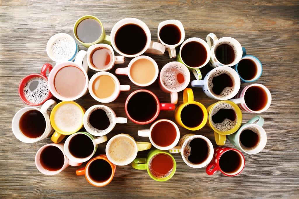 Adskillige kopper indholder koffeinholdige drikke står på et træbord