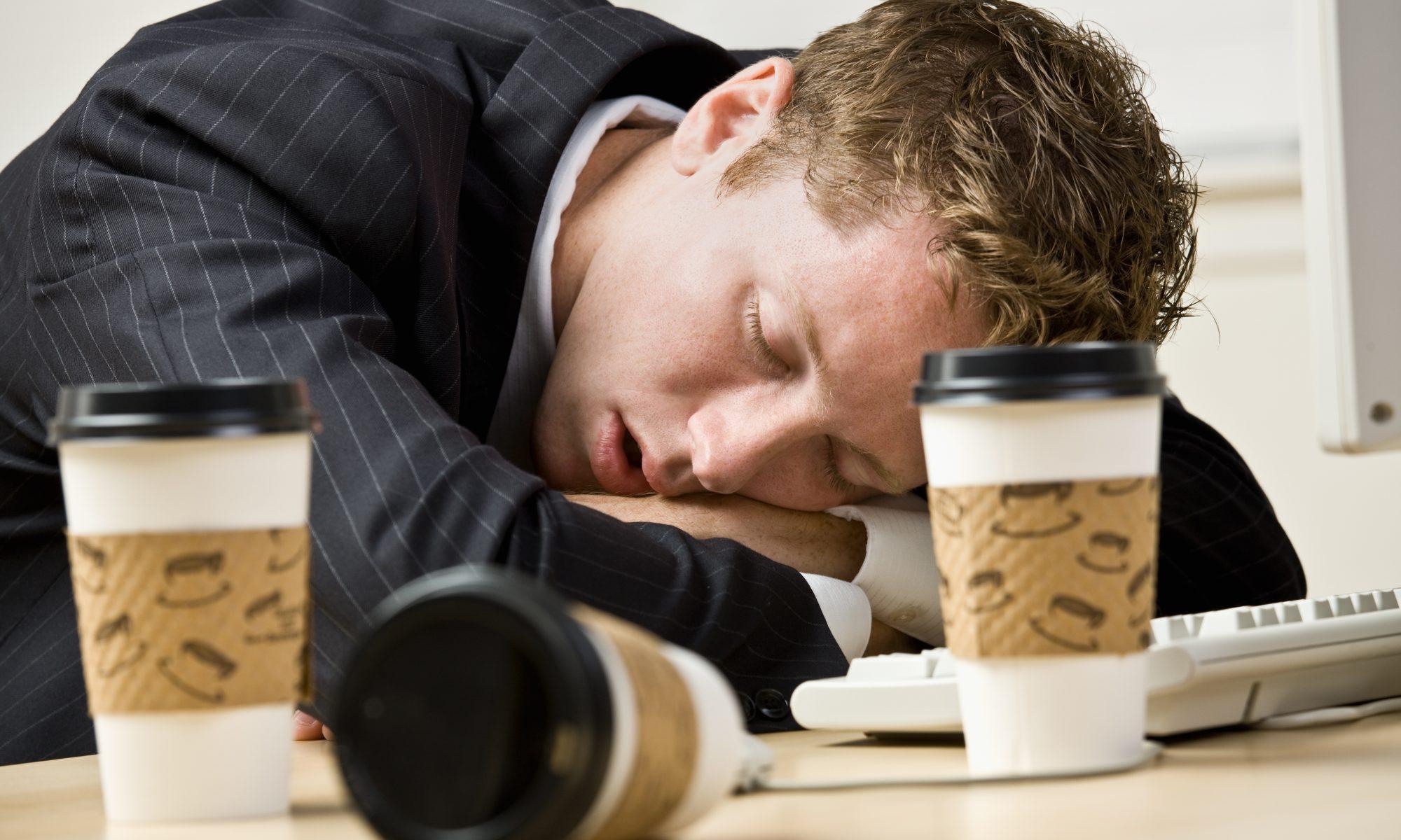 Mand i jakkesæt sover på skrivebordet, på trods af flere kopper kaffe